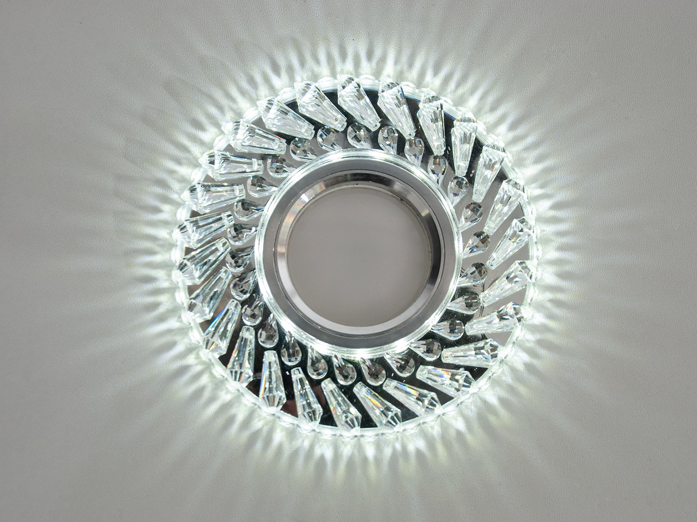 Точечные светильники со светодиодной подсветкой настоящий хит нашего времени, к привычному освещению с помощью ламп MR-16 добавлена светодиодная подсветка, мощностью 3Вт. Вы можете включать как по отдельности лампу или подсветку, так и вместе. Врезка выполнена из акриловой смолы, которая не уступает по своим декоративным свойствам хрусталю — на потолке вы увидите красивые лучики света. Точечные светильники с led подсветкой широко применяются практически в любых помещениях — гостиных, спальнях, кухнях, коридорах и даже в ванной комнате. Лампа и трансформатор в комплект не входят.